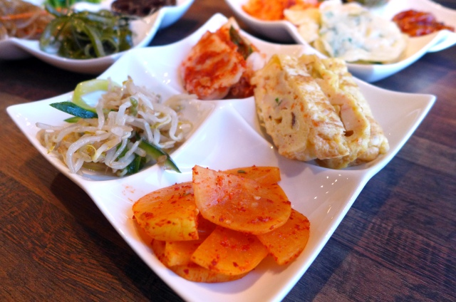 Banchan plate: Pickled Chinese radish, bean sprout salad, kimchi, Korean egg roll