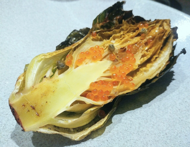 Baby romaine cooked over a fire, basted in black garlic butter topped with fermented wild onion blossoms and trout roe