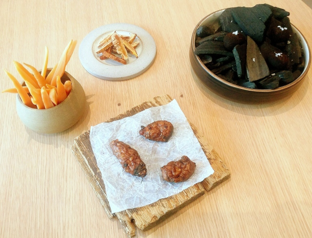 Snacks (Clockwise L to R): Pickled carrots, Dried fermented peach, Quail egg rolled in vegetable ash, Fried sunchoke skin